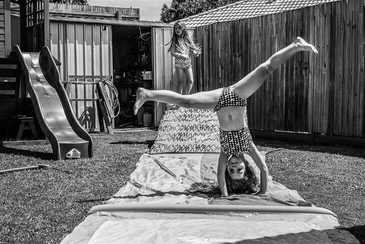 Little girl doing a cartwheel in front of her sister.