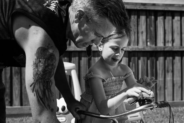 Dad and daughter cleaning her bike.
