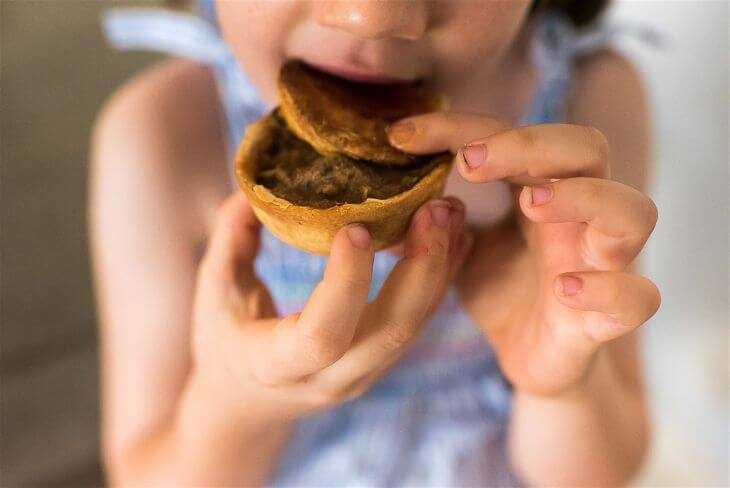Girl eating a mini meat pie.
