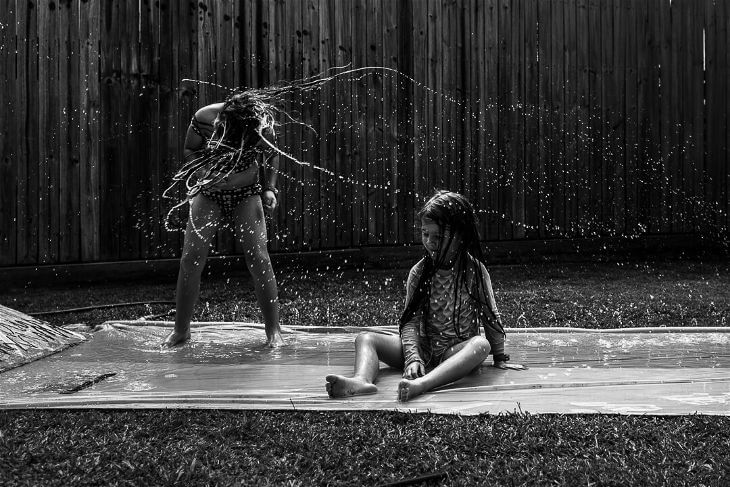 Girl splashing her sister with wet hair.