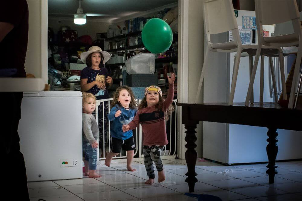Kids chasing green balloon in the house