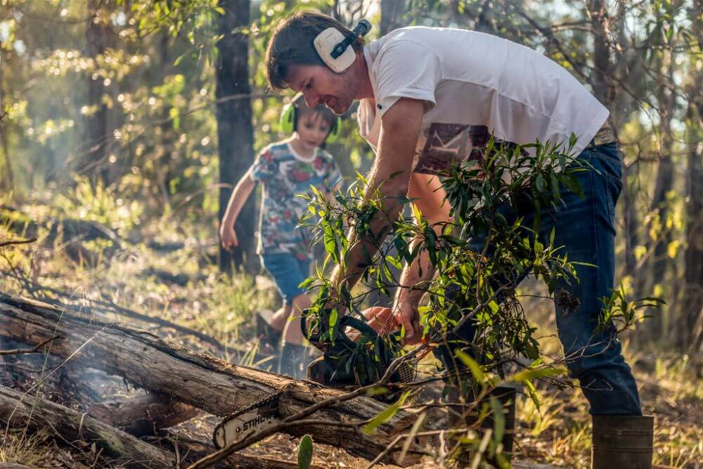 Farther and son cutting the fire wood at documentary family photography session